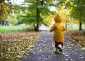 jongen in de regen met regenjas en laarzen